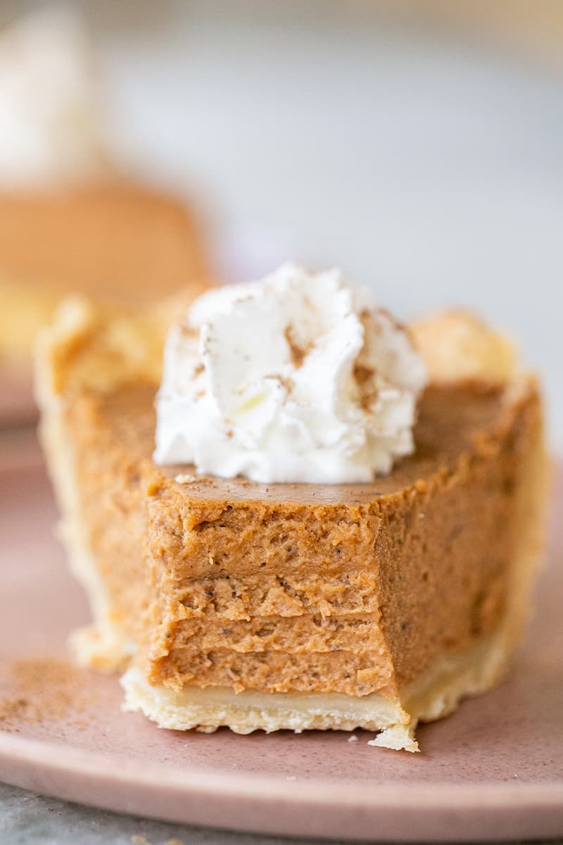 Slice of pumpkin pie with bite taken out of it.