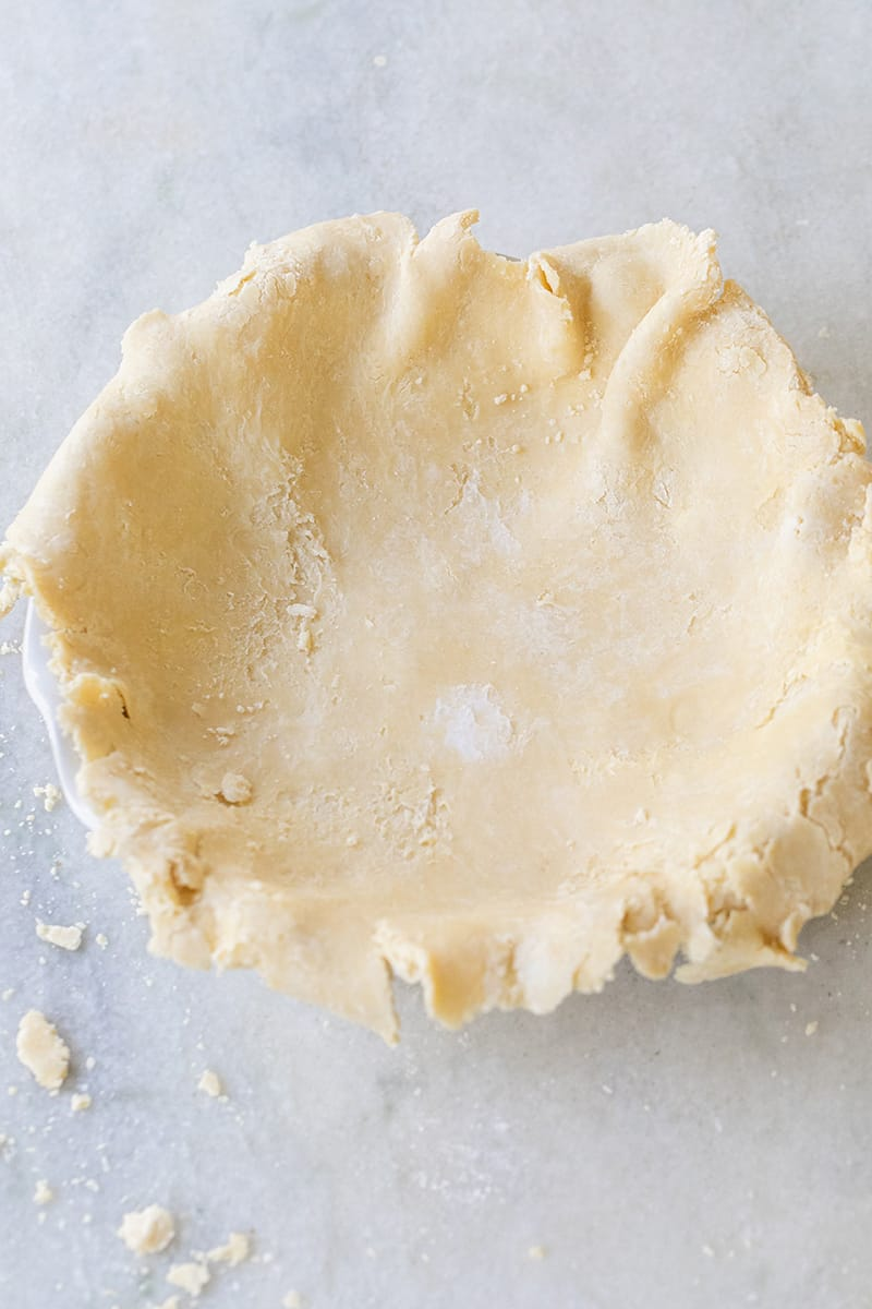 Pie crust rolled out and set on a pie dish about to be formed into pie crust.