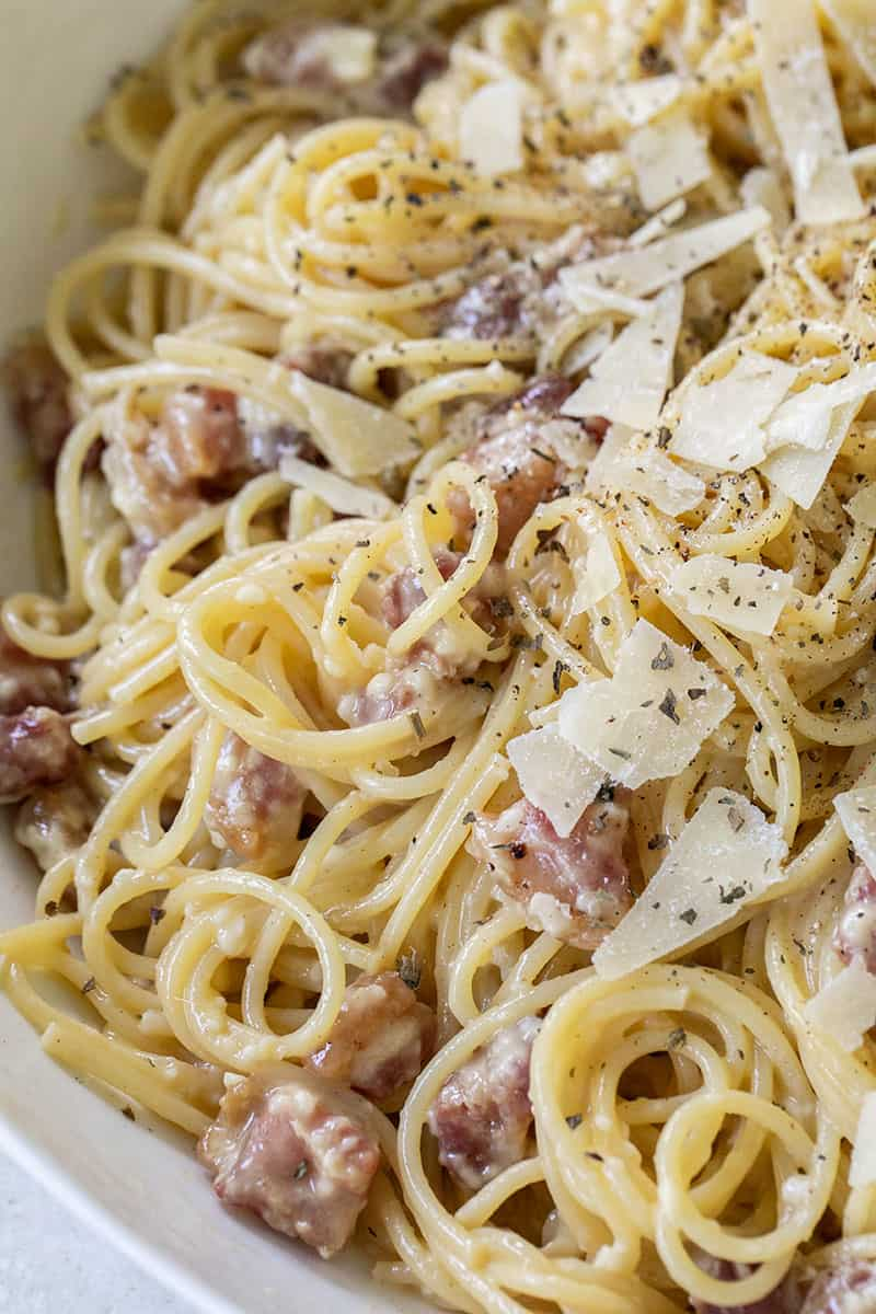 Easy Carbonara pasta recipe with egg, cream and pancetta. Served in a  white bowl.