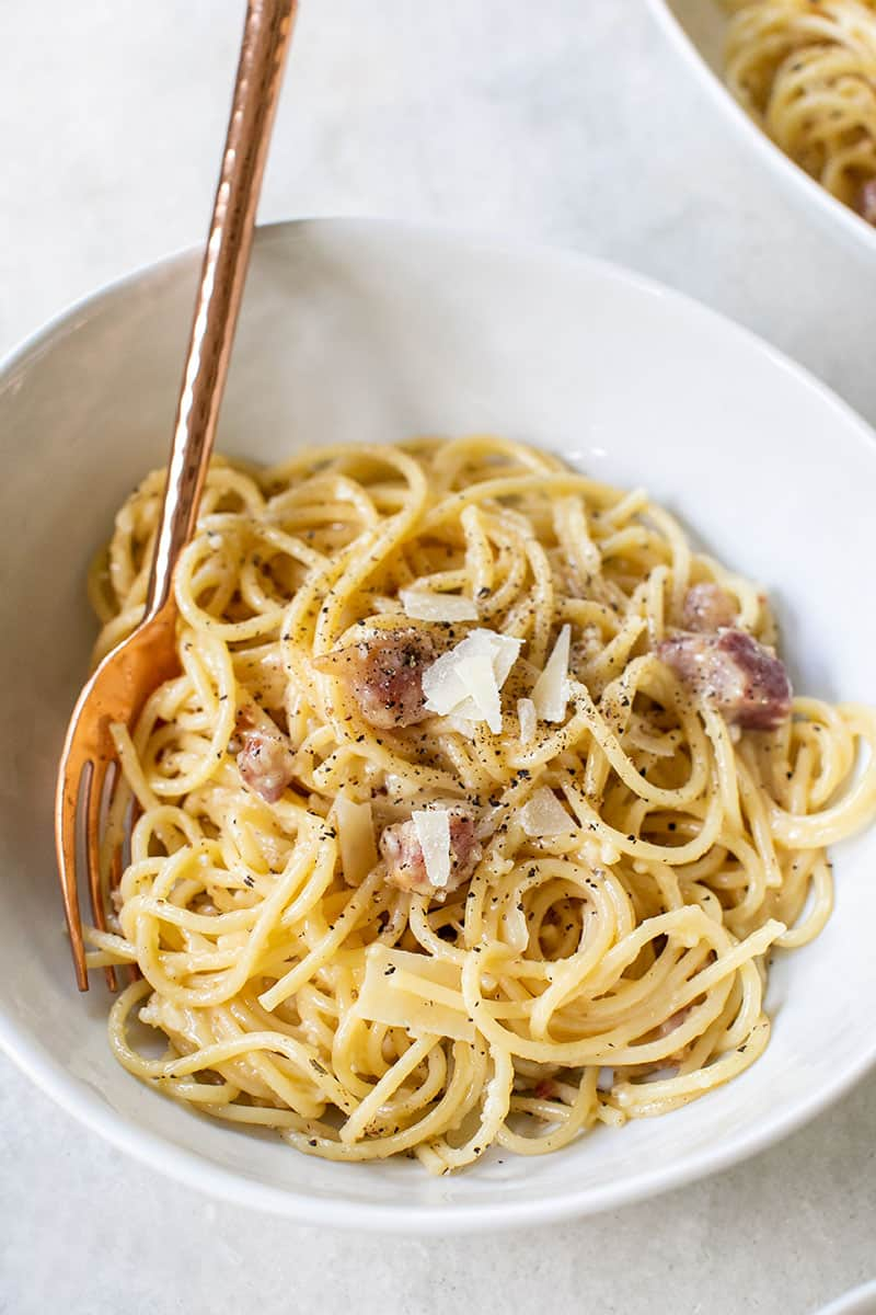 Bowl of spaghetti carbonara with bacon and parmesan cheese. Served in a white bowl with a copper fork.