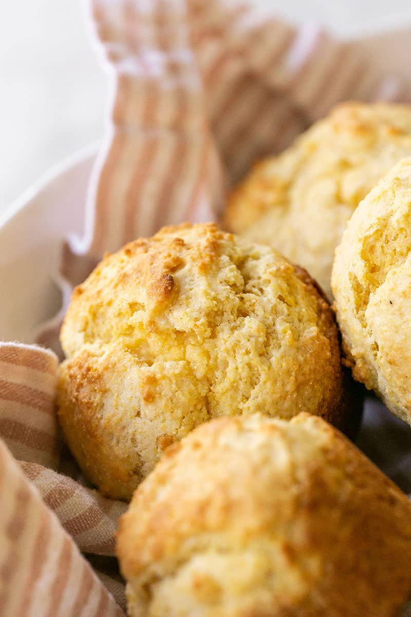 Easy cornbread muffin recipe and cornbread muffins in a bowl with a pink stripe towel.