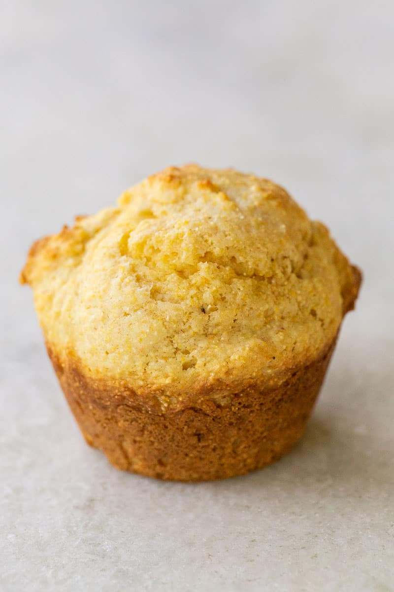 One cornbread muffin on a marble table.