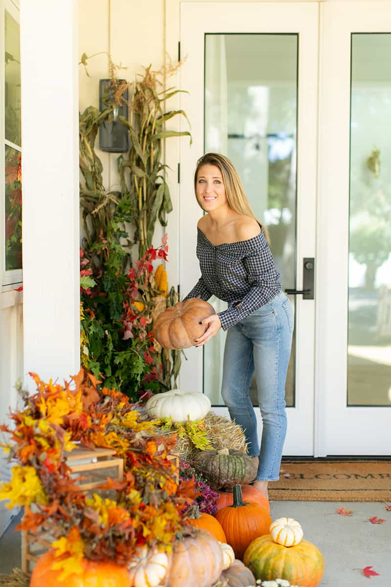 Eden Passante holds a fairytale pumpkin on her fall front porch.
