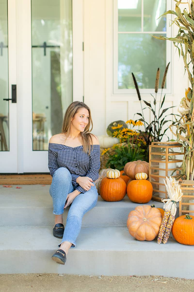 Eden Passante of Sugar and Charm sitting on her fall front porch with pumpkins.