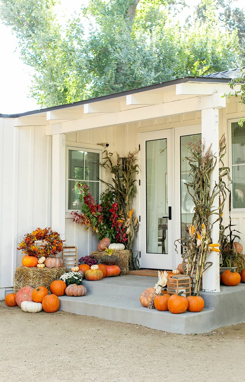 Beautiful fall porch with hay bales, corn, flowers and a lot of pumpkins.