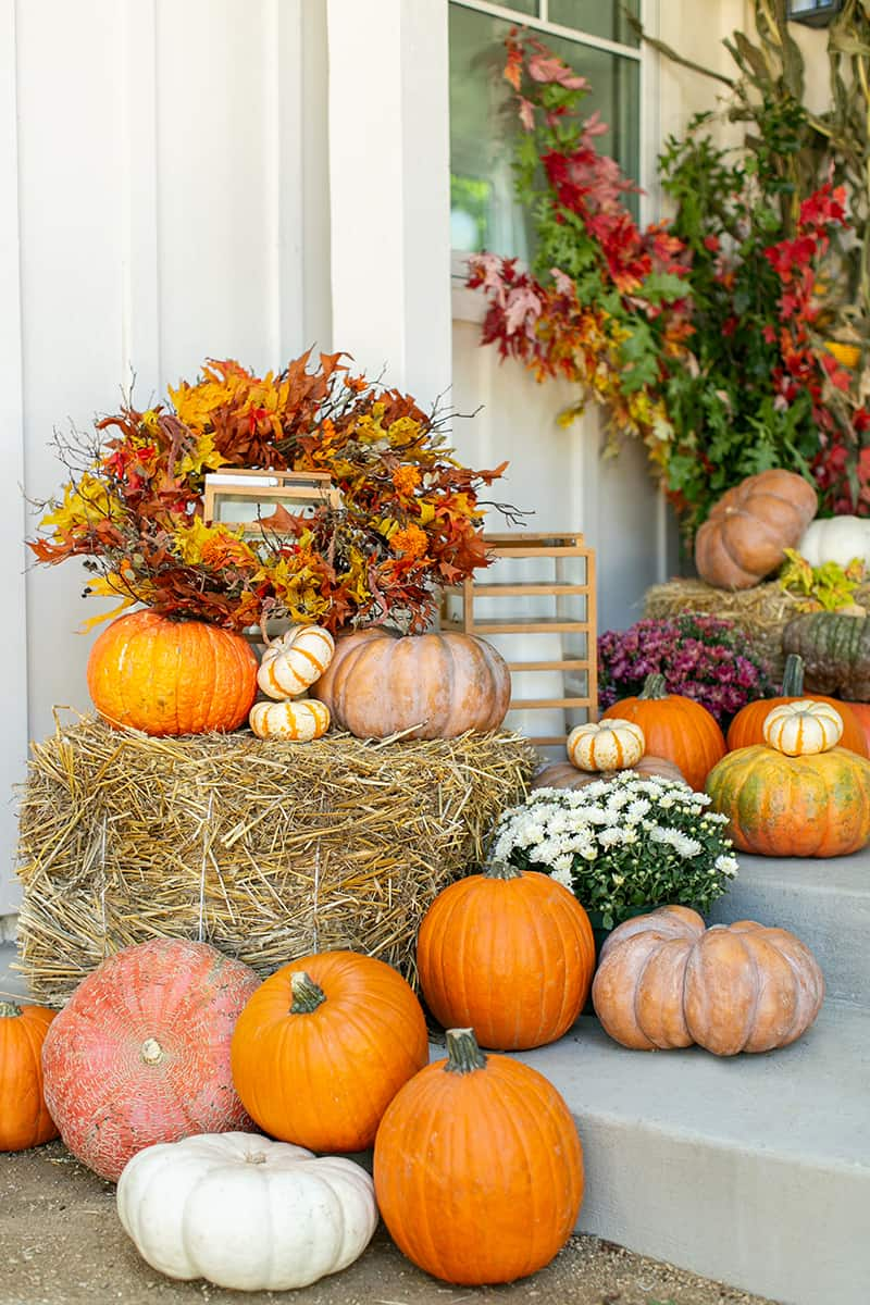 Fall porch ideas with an array of pumpkins, mums and hay bales.