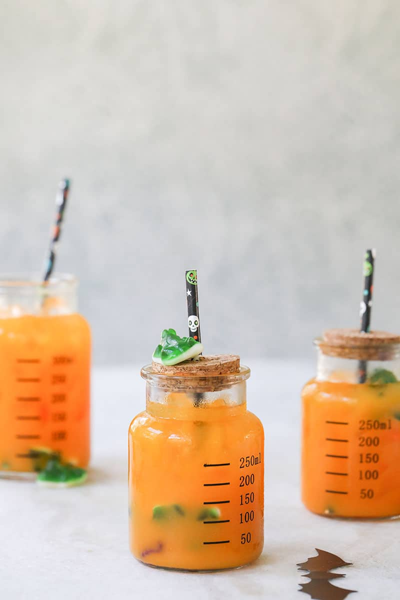 Halloween kids party punch in glass jars with halloween straws and frog gummies.