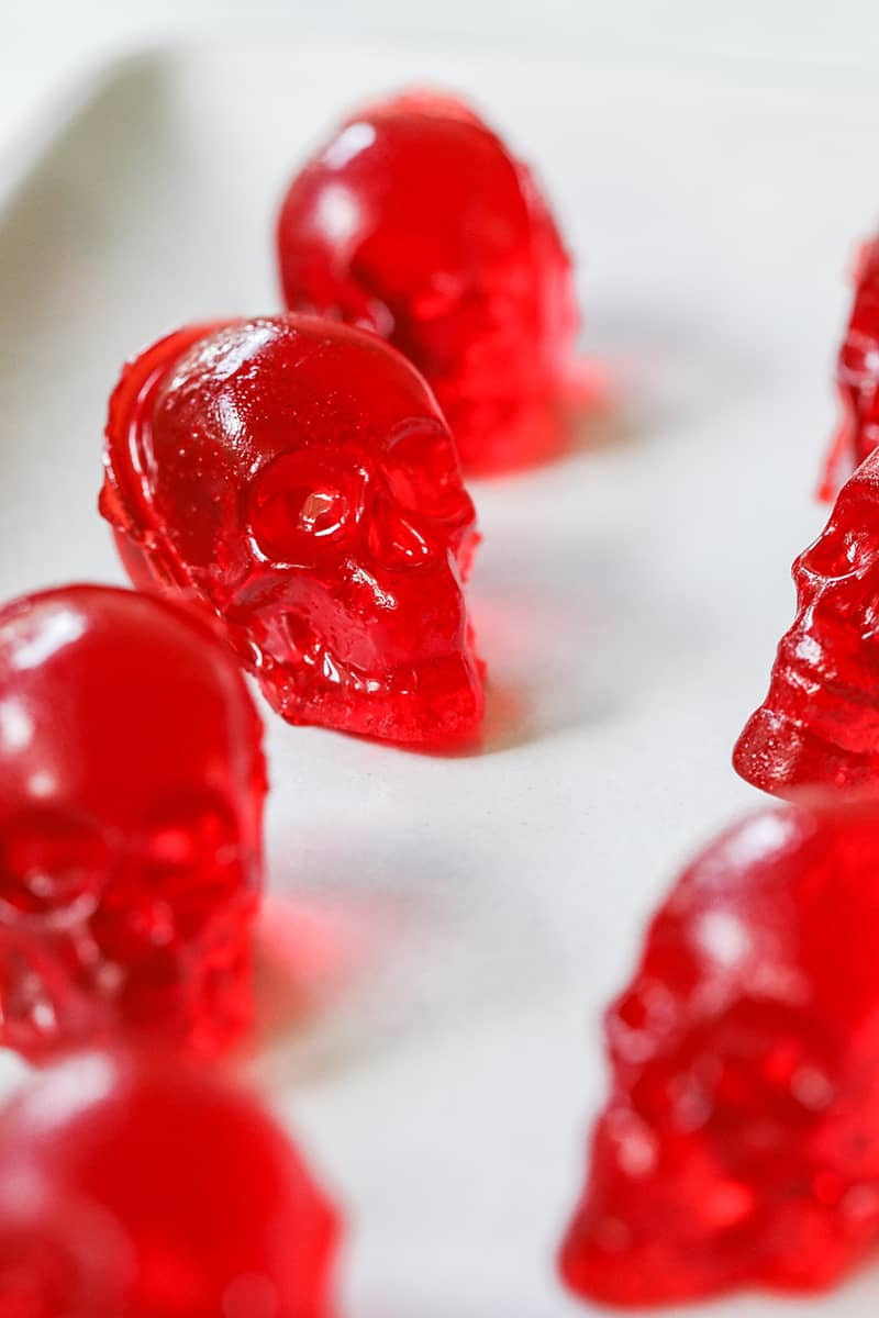 Bright red skull jello shots on a white plate.