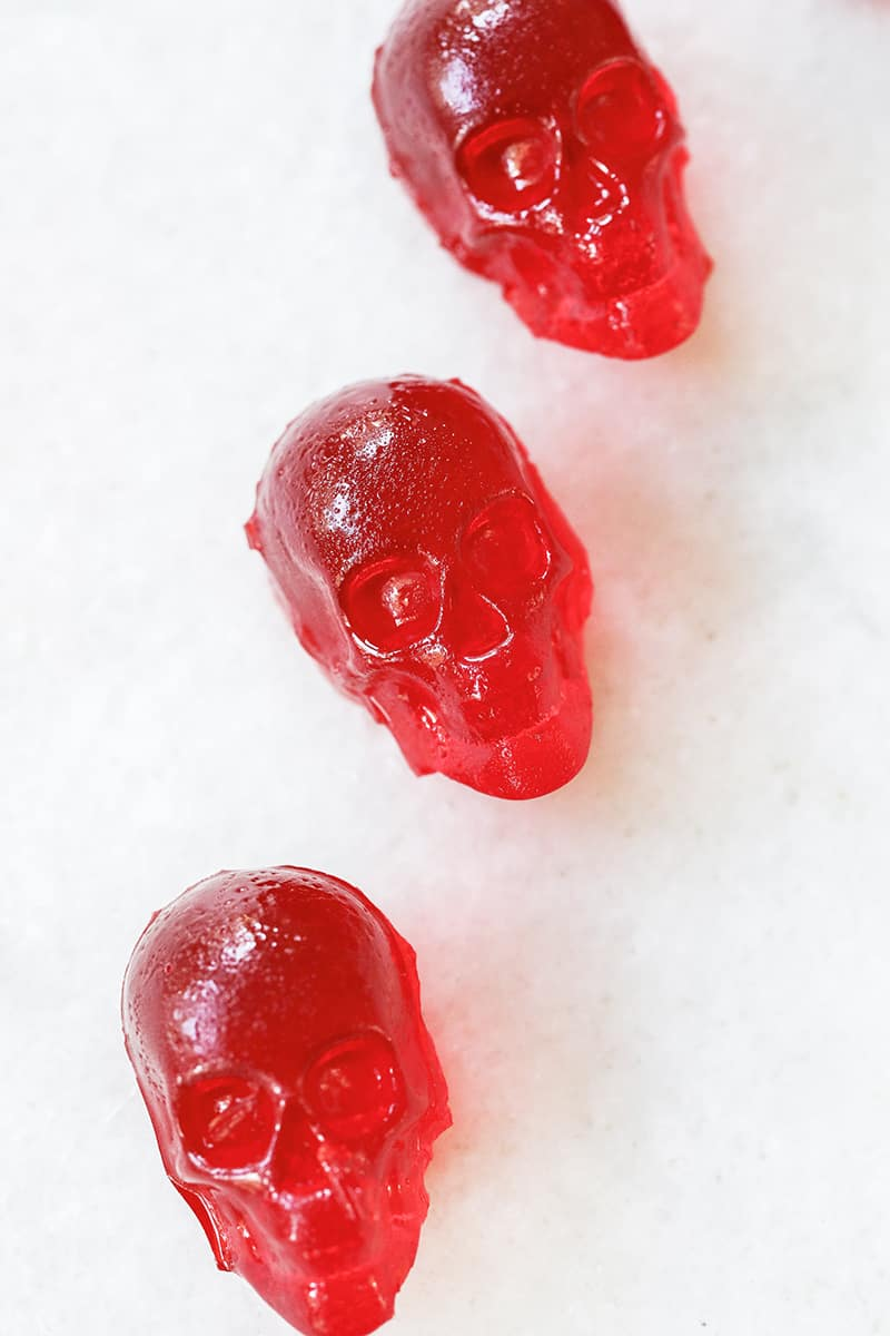 Bright red cherry jello shots shaped like skulls on a marble table.