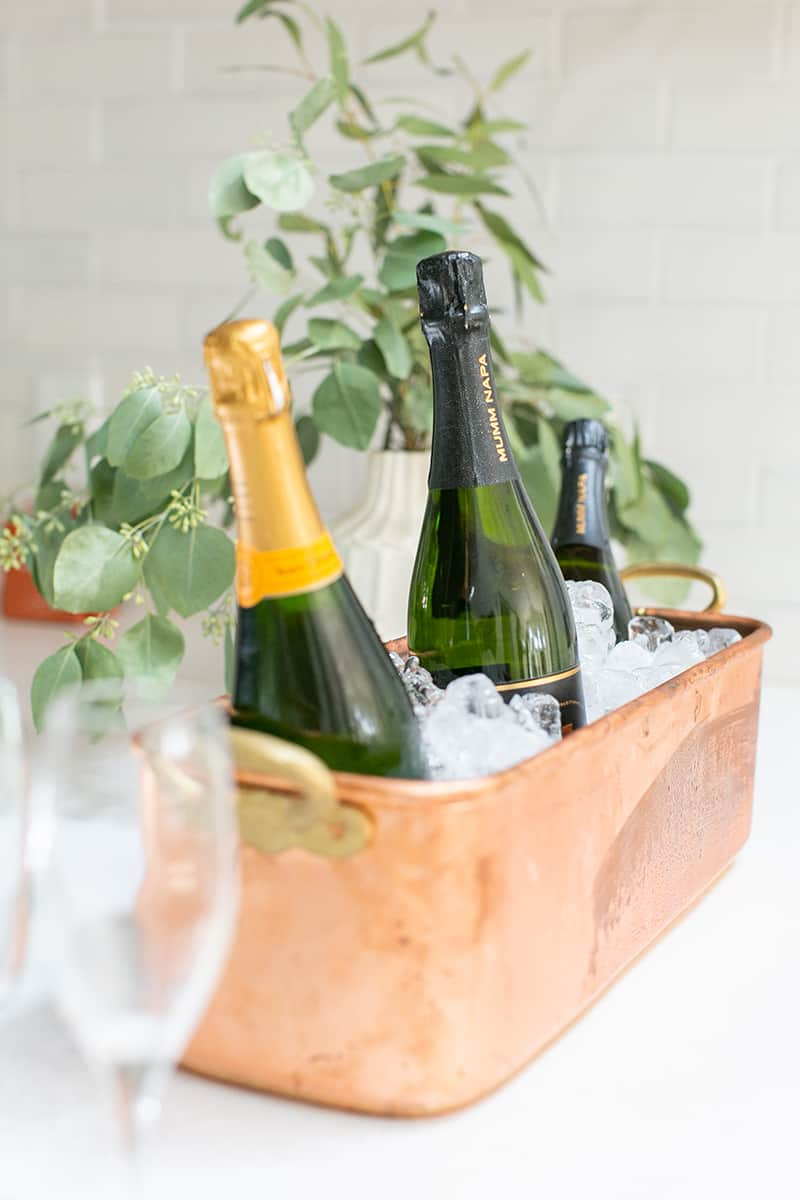 Bottles of Champagne in brass ice bucket from Williams Sonoma.