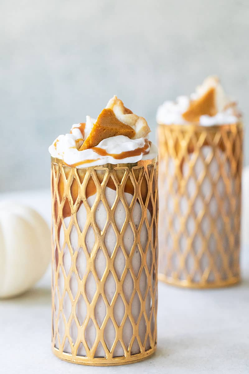 Pumpkin Pie milkshake in a tall gold glass with whipped cream, caramel and a slice of pumpkin pie.
