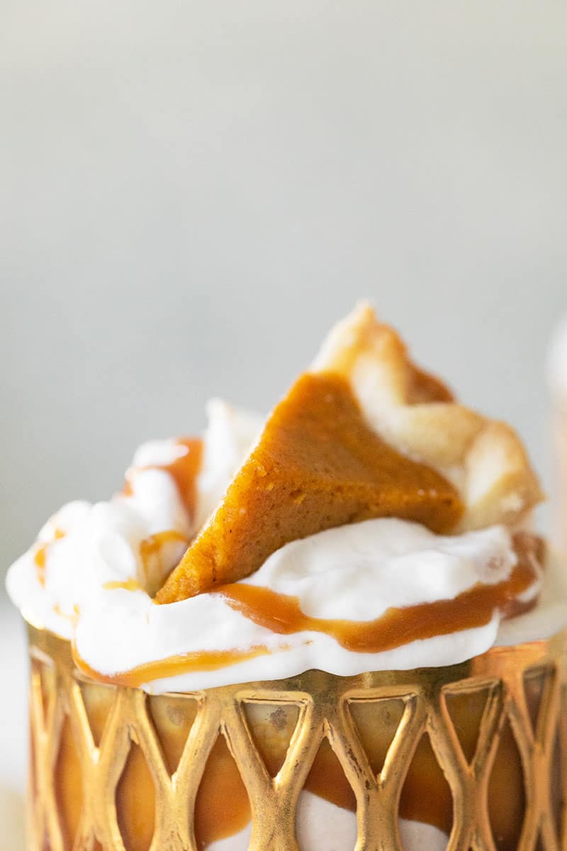 Close up of a pumpkin pie milkshake with a mini slice of pumpkin pie.