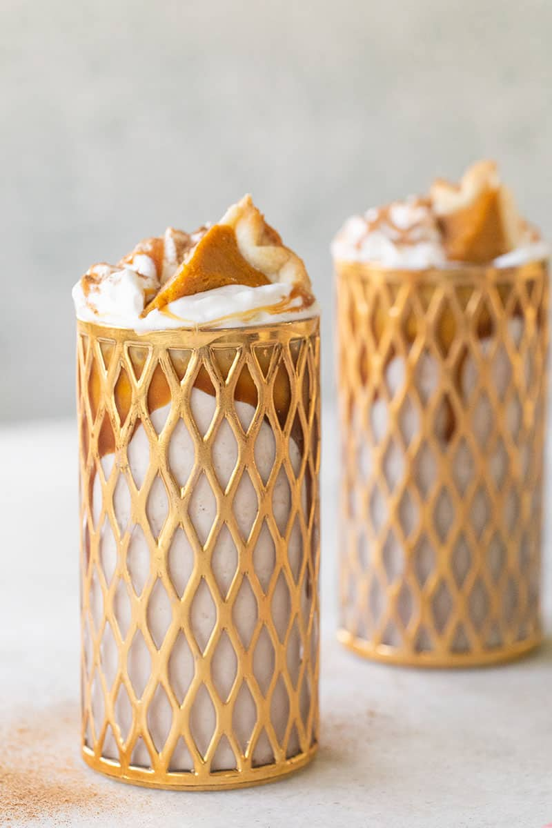 Two Pumpkin Pie Milkshakes with bourbon. Topped with whipped cream, caramel and a small slice of pumpkin pie.