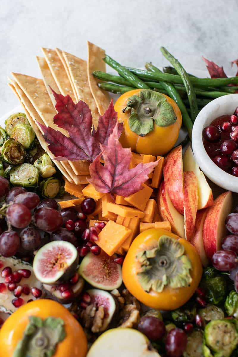 Thanksgiving appetizer board with cheese, fruit, roasted vegetables and cranberry sauce.