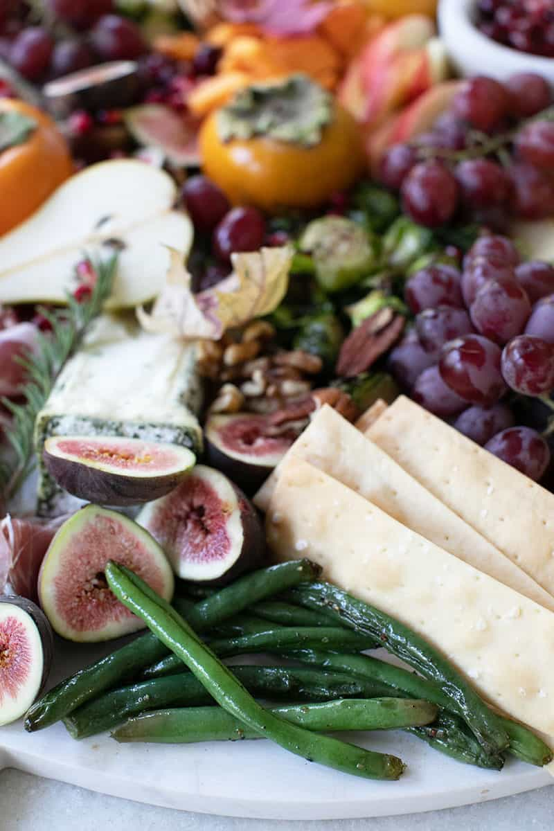Green beans, crackers and figs on a board.