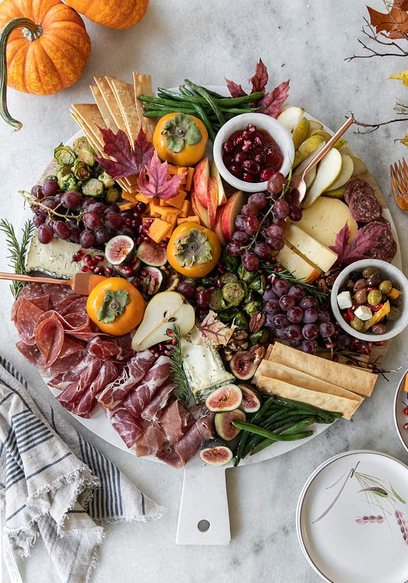 Large round platter filled with cheese, fruit, meat, crackers for an easy Thanksgiving appetizer.