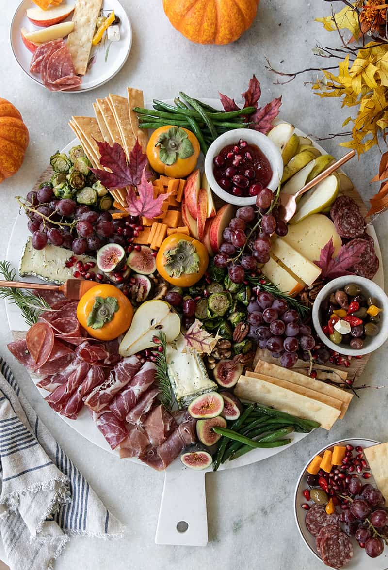 Best Thanksgiving appetizer recipe with cheese, meat and crackers on a giant marble board.