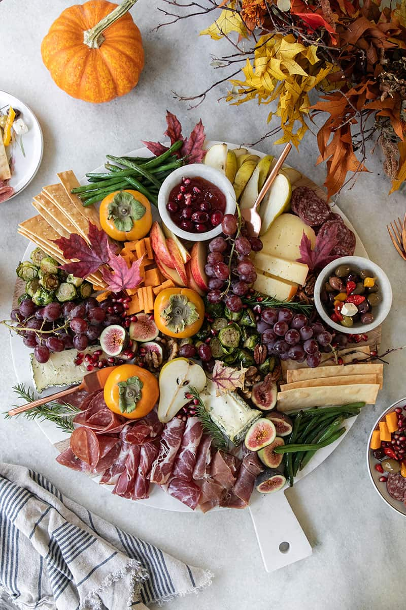 A Thanksgiving appetizer cheeseboard with fruit, cheese, meat, crackers, olives and more. On a marble table with fall leaves.