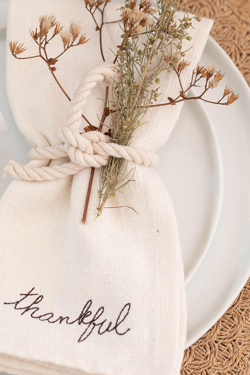 "Linen napkin with ""thankful"" written on it tied with a rope."