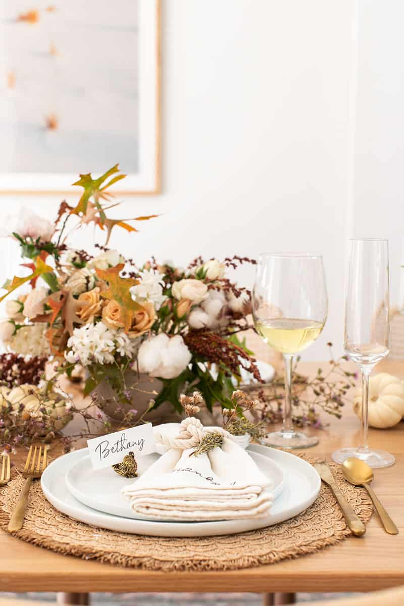 Thanksgiving table setting with flowers, white wine, white plates and napkins.