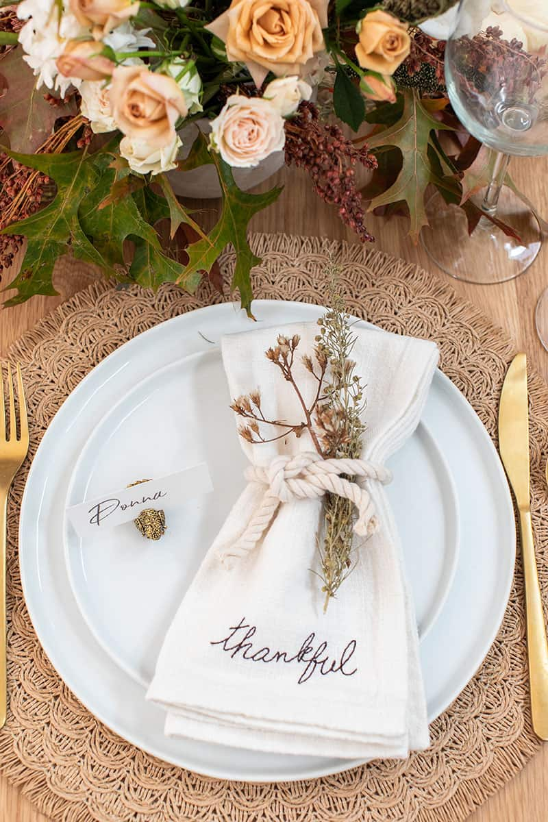 Thanksgiving table setting with thankful napkins, gold silverware and rope.