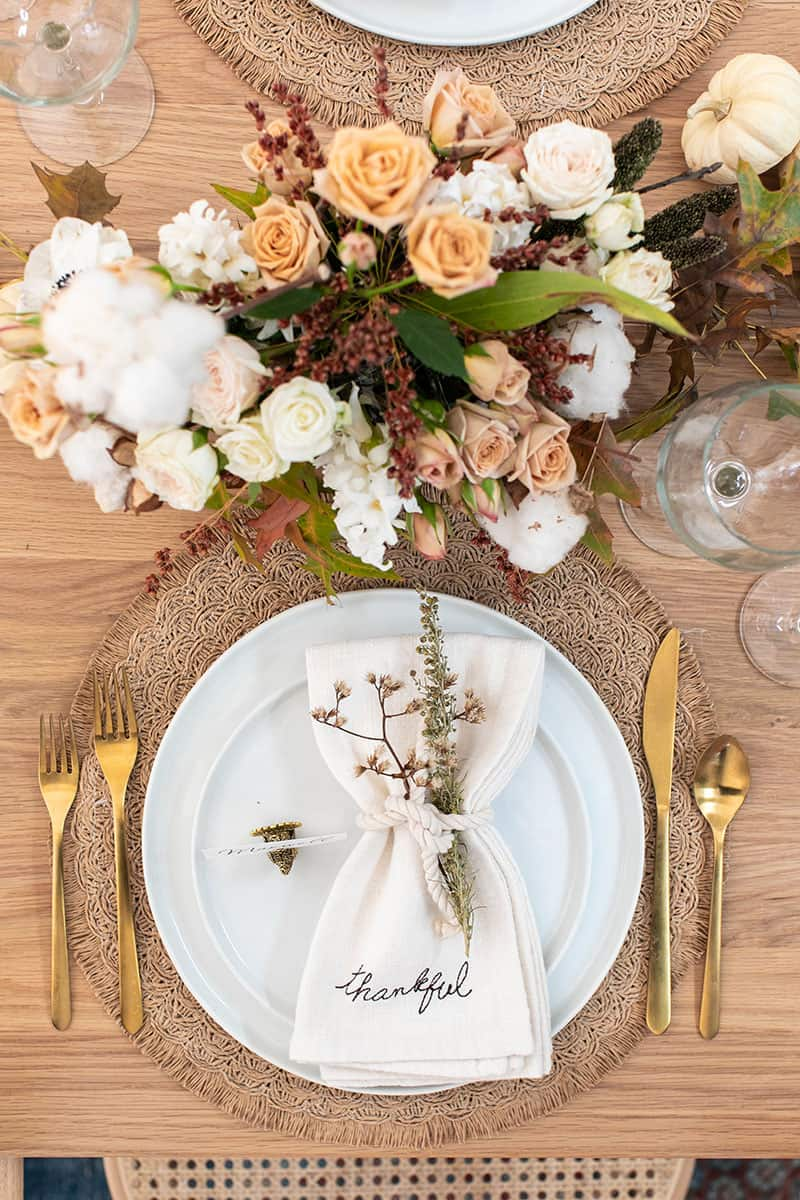 Thanksgiving table decor and table setting. White napkins, white plates, flowers, gold flatware and wine glasses.