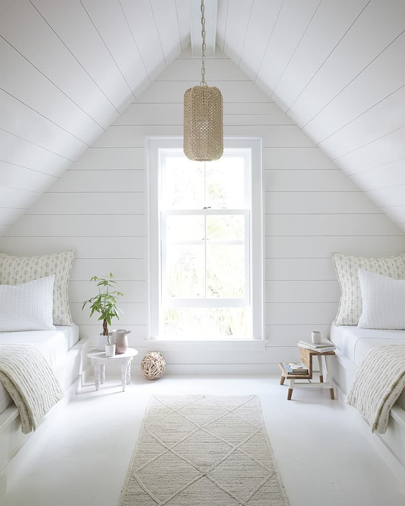 White A-Frame bedroom with shiplap and white twin beds.