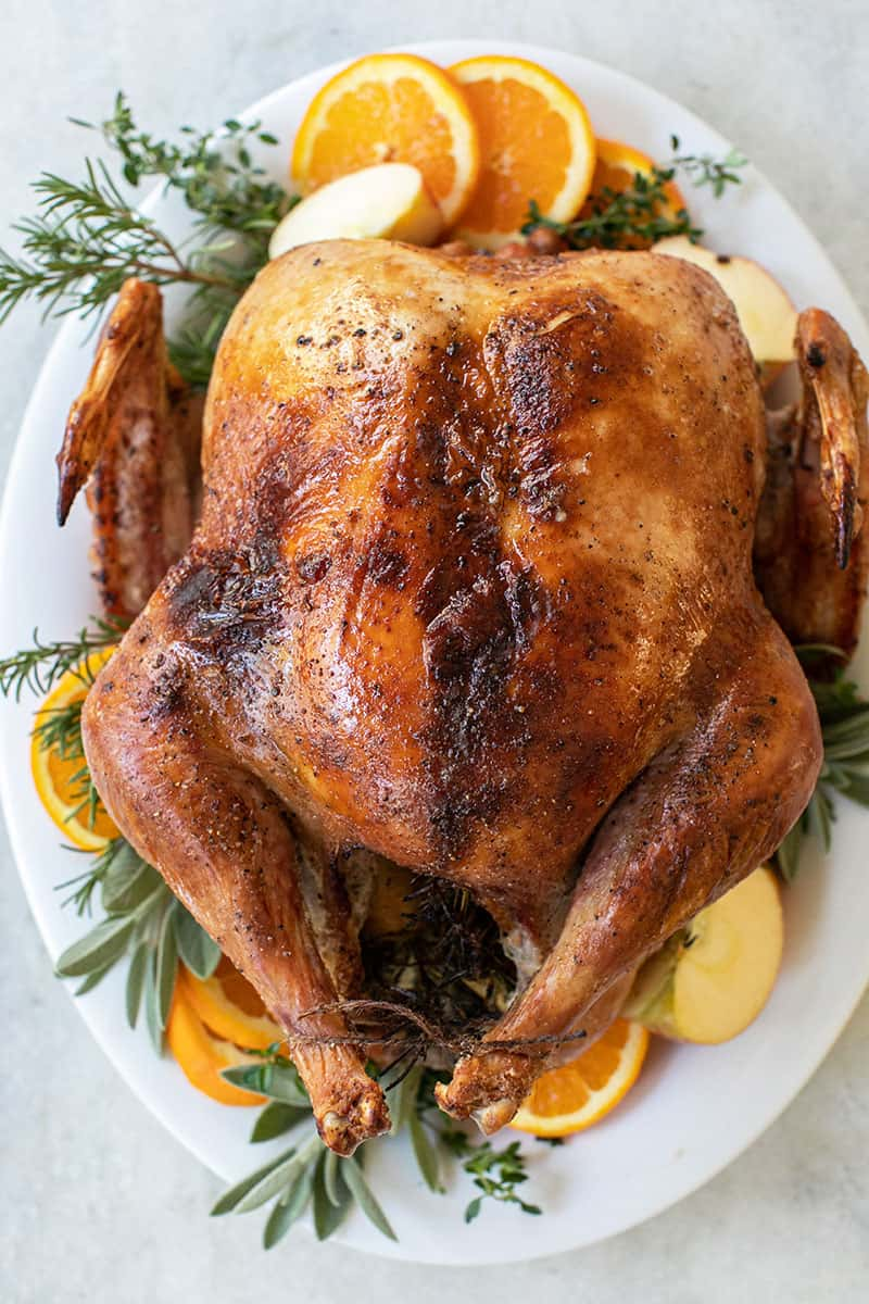 How to Cook a Turkey Guide. A Golden brown turkey plated with orange slices, thyme, rosemary.