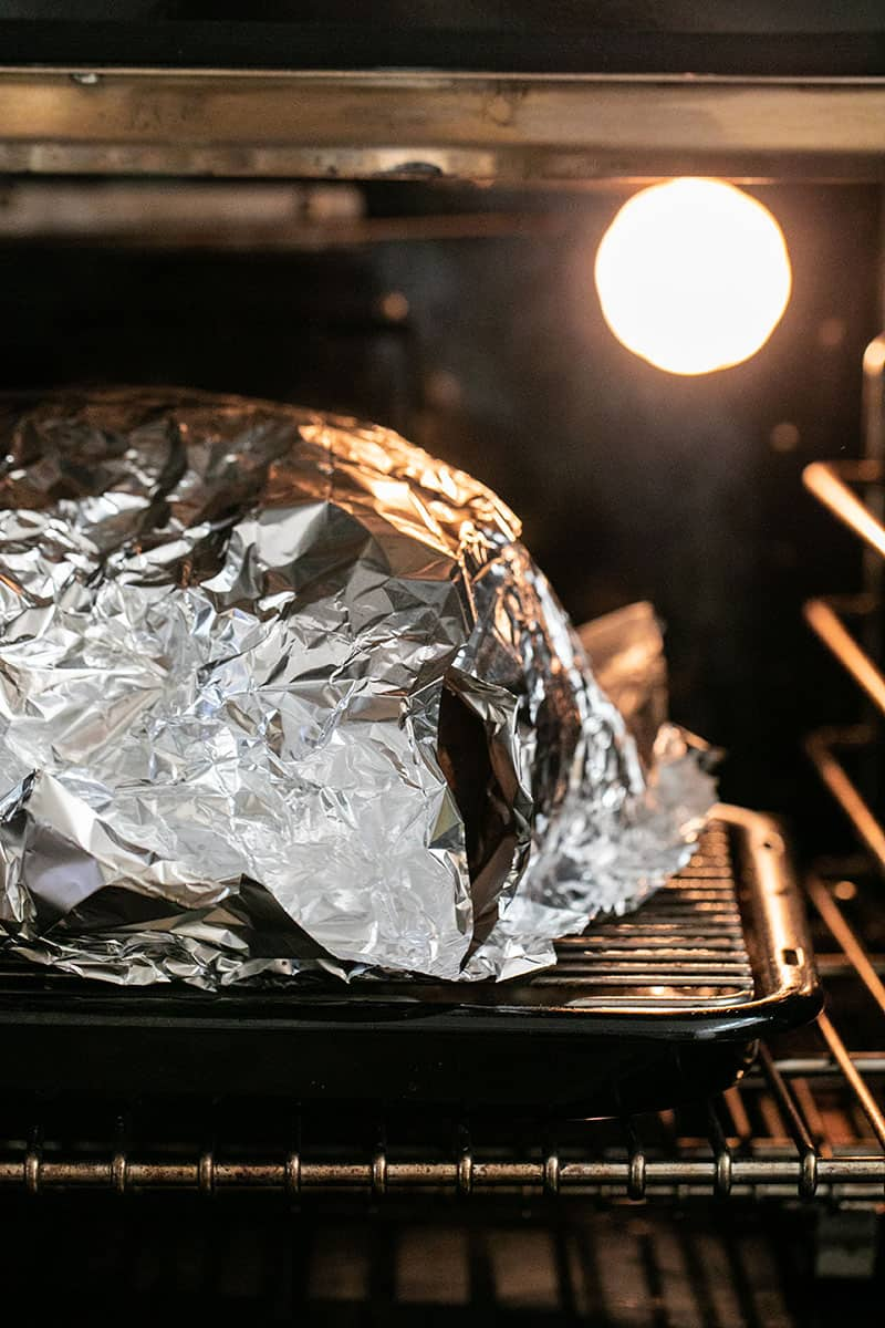 Covering a turkey in the oven with tin foil. A guide to how to cook a turkey.
