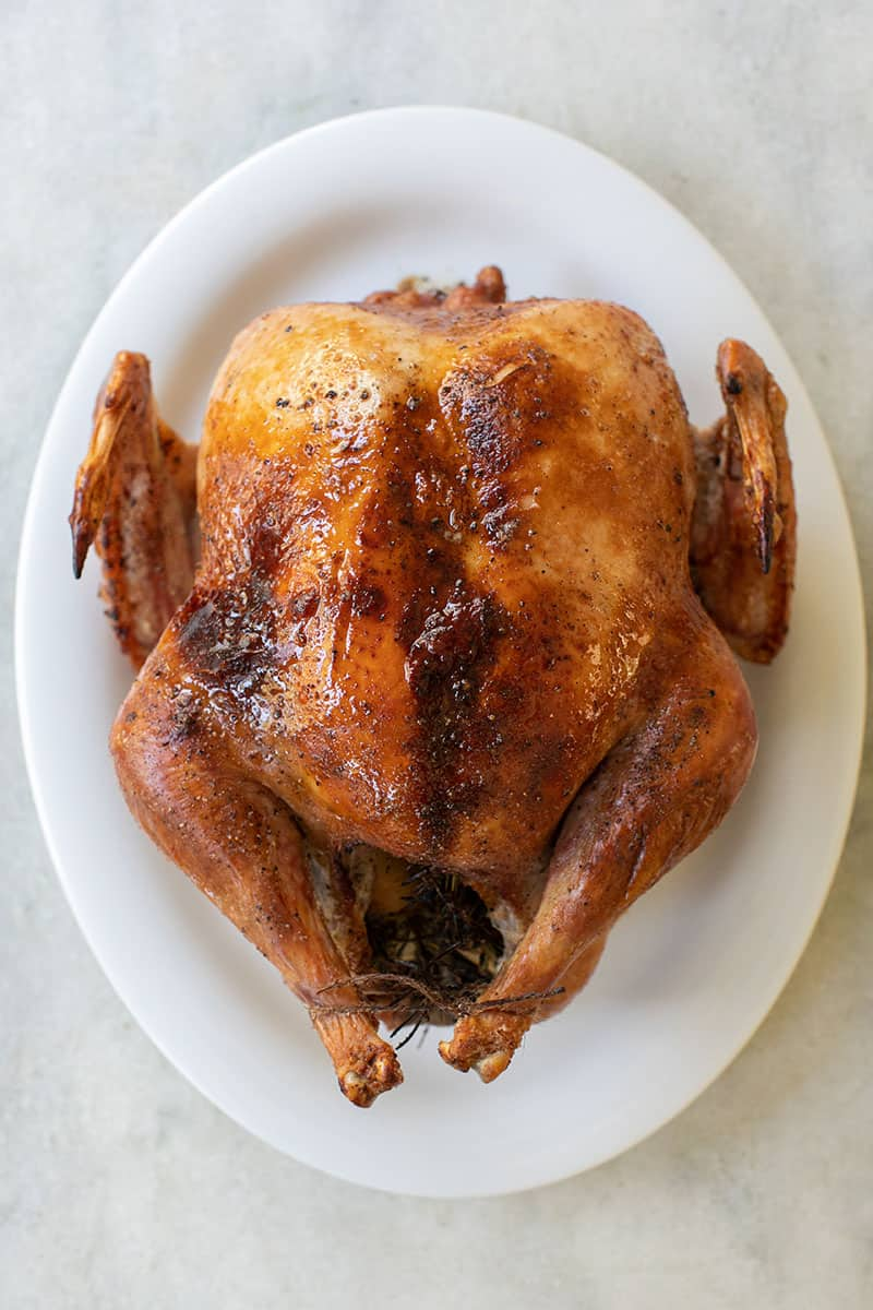 A guide for how to cook a turkey and a turkey on a white platter.