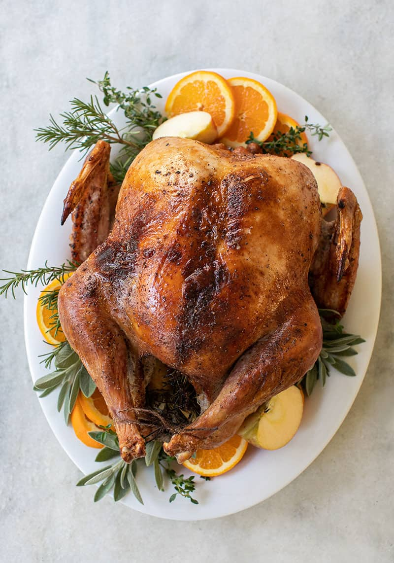 A golden brown turkey on a platter with orange slices, sage, thyme and apples.