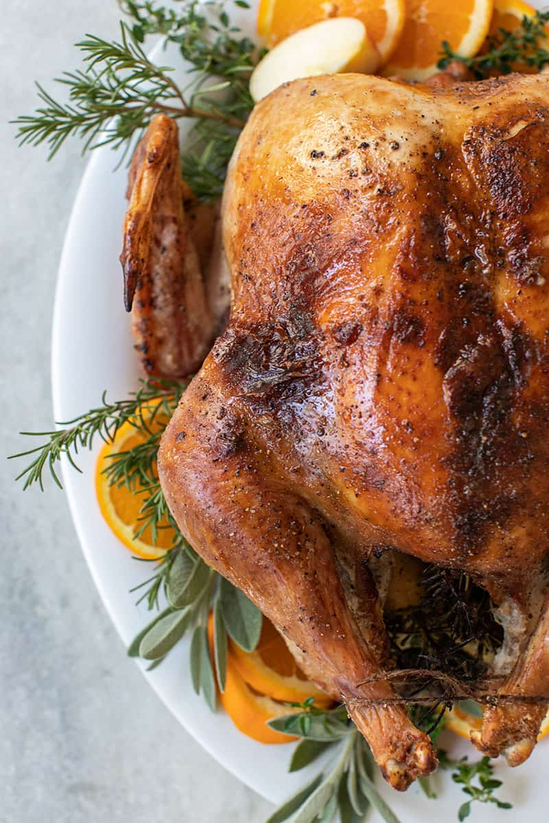A golden brown, cooked turkey plated with sage, thyme, orange slices, rosemary.