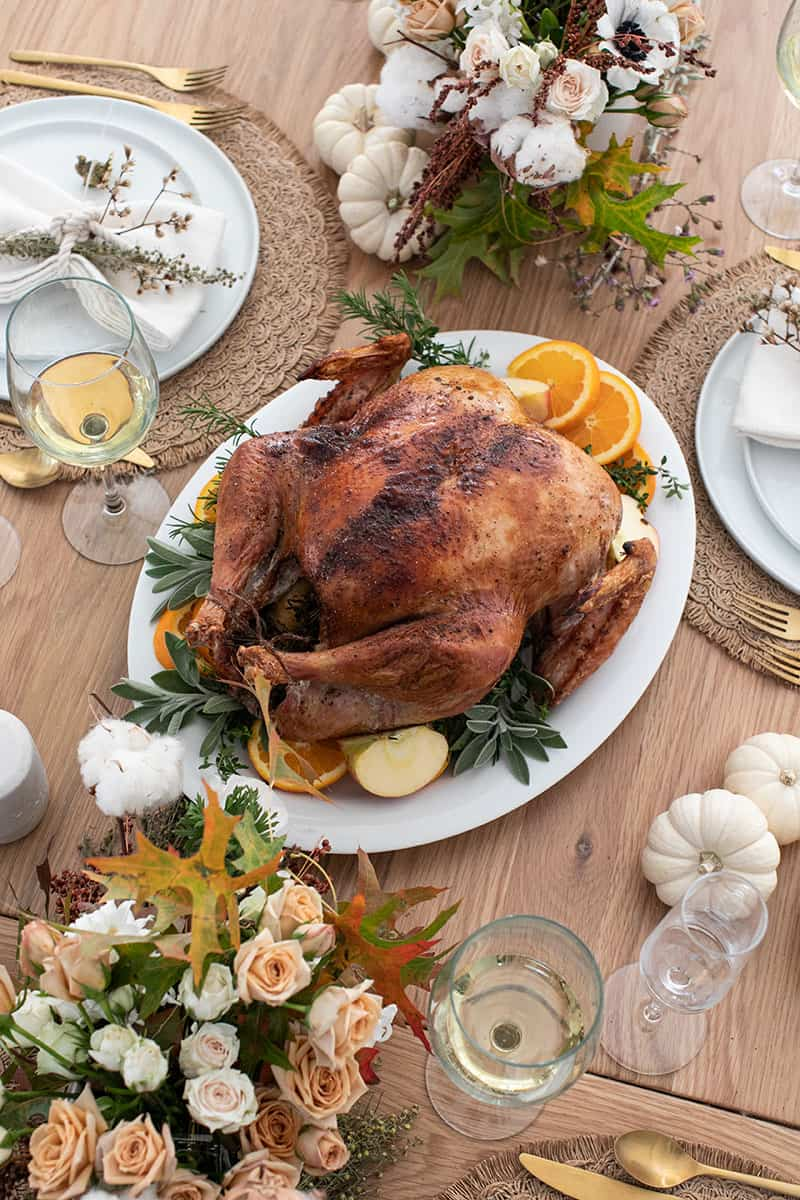 A roasted turkey on a platter on a Thanksgiving table setting.