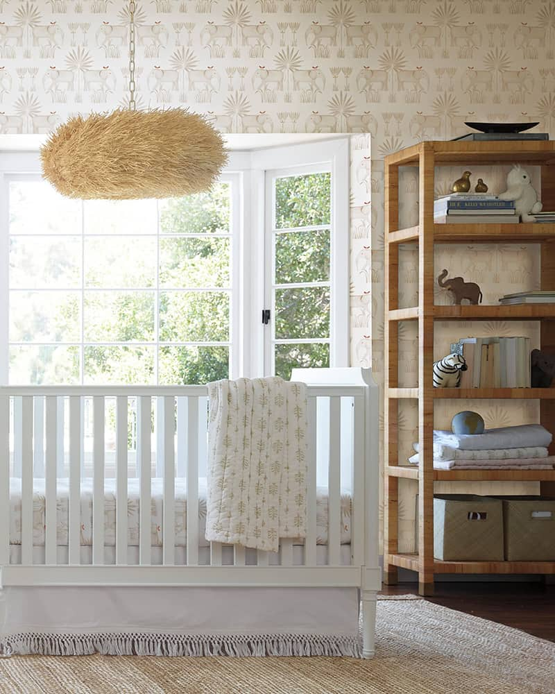 A baby nursery with crib, wallpaper and hanging lights.