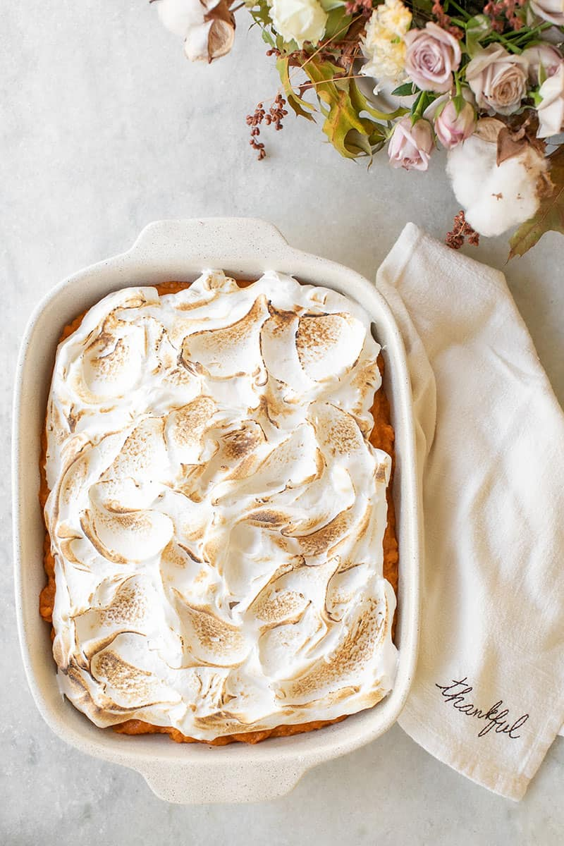 Overhead of sweet potato casserole with marshmallow fluff and a napkin that reads Thankful.