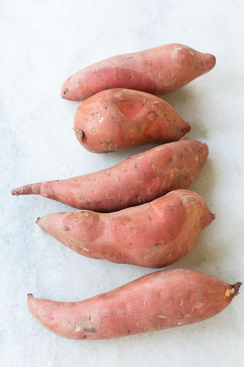 Five sweet potatoes lines up in a row on a marble table.