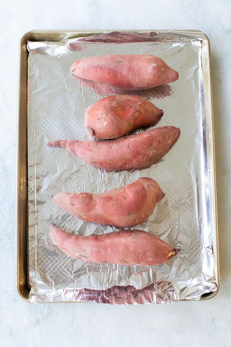 Five sweet potatoes on a baking sheet lined with foil.