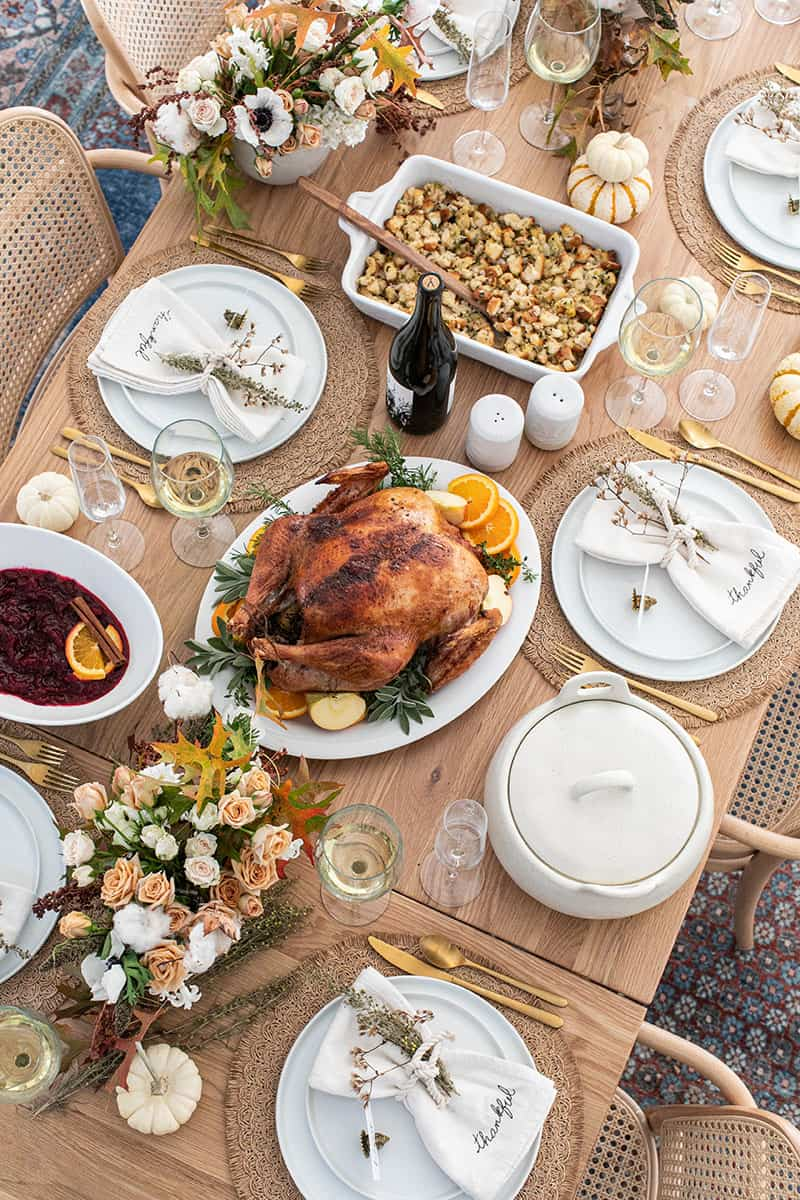Thanksgiving table setting with a turkey, flowers, wine, wine, stuffing, cranberry sauce.
