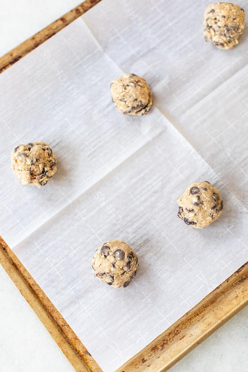 Cookies rolled on a cookie sheet.