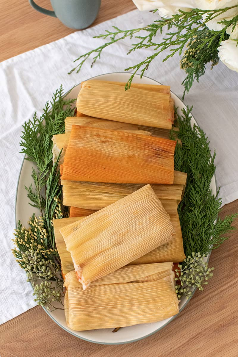 Tamales on a green and white platter with Christmas greens on the plate.