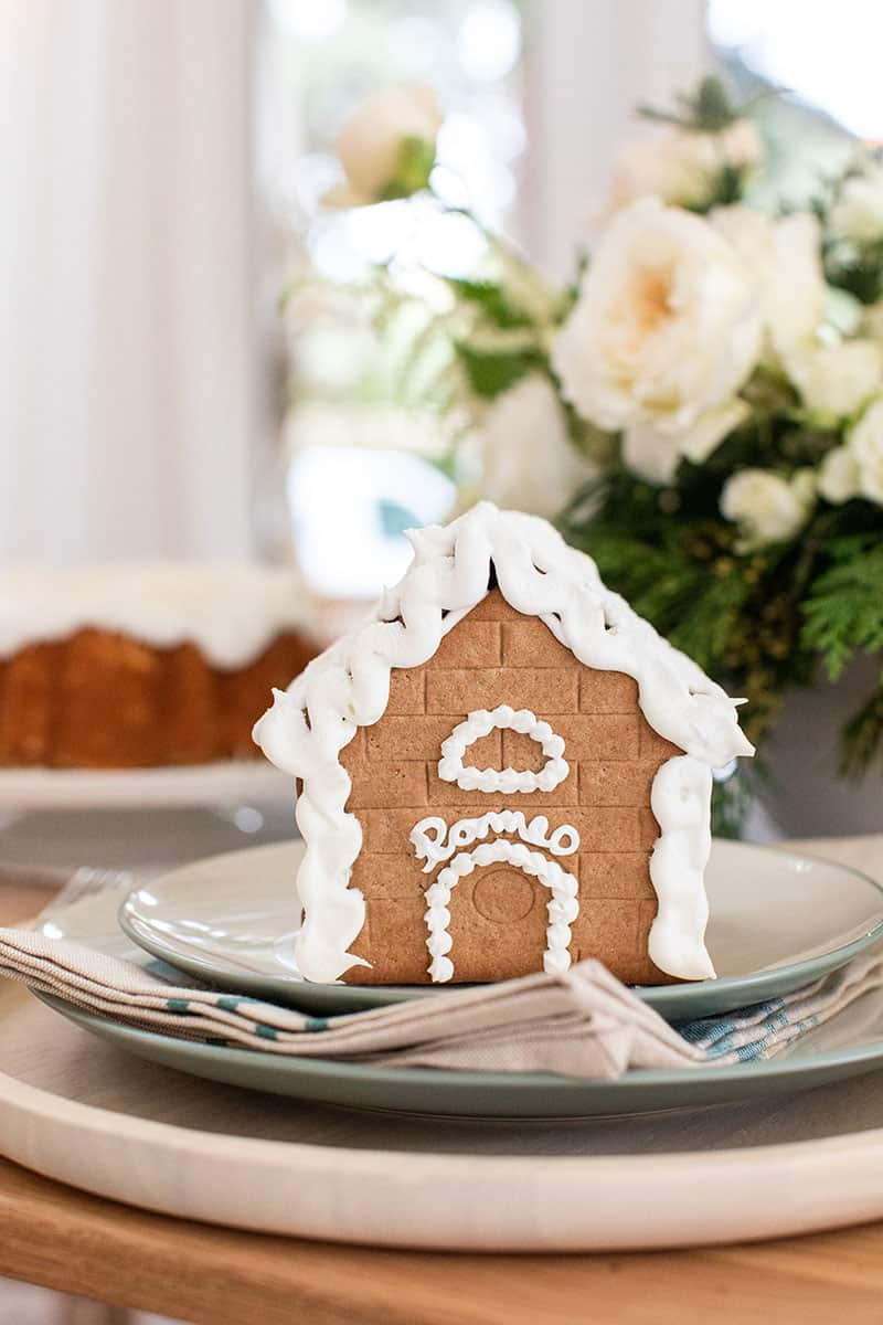 Gingerbread house on a Christmas Table Setting with Romeo written on it in frosting.