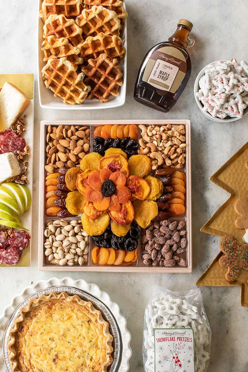 Dried fruit, meat, quiche and more holiday food on a marble table all from Harry & David.