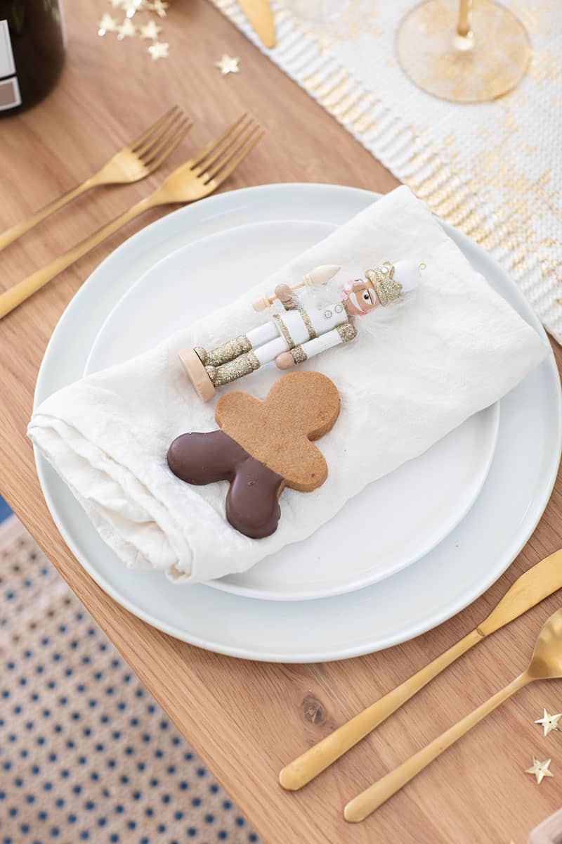 Nut cracker and gingerbread cookie on a place setting with gold flatware.