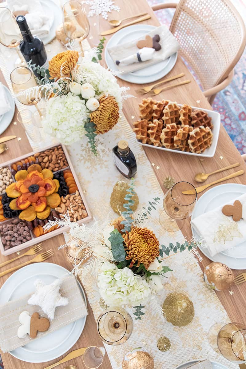 Christmas brunch table setting with flowers, waffles, wine, fruit.