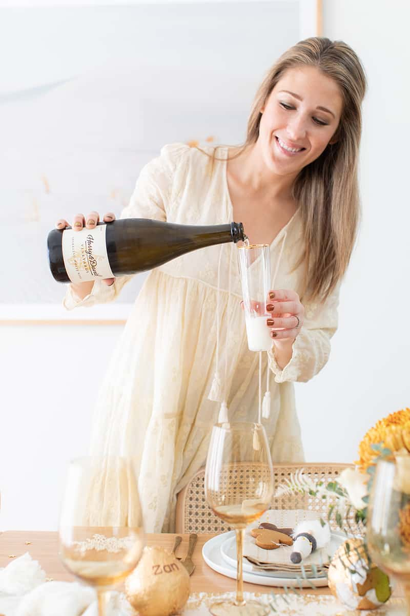 Eden Passante pouring a glass of sparkling white wine.