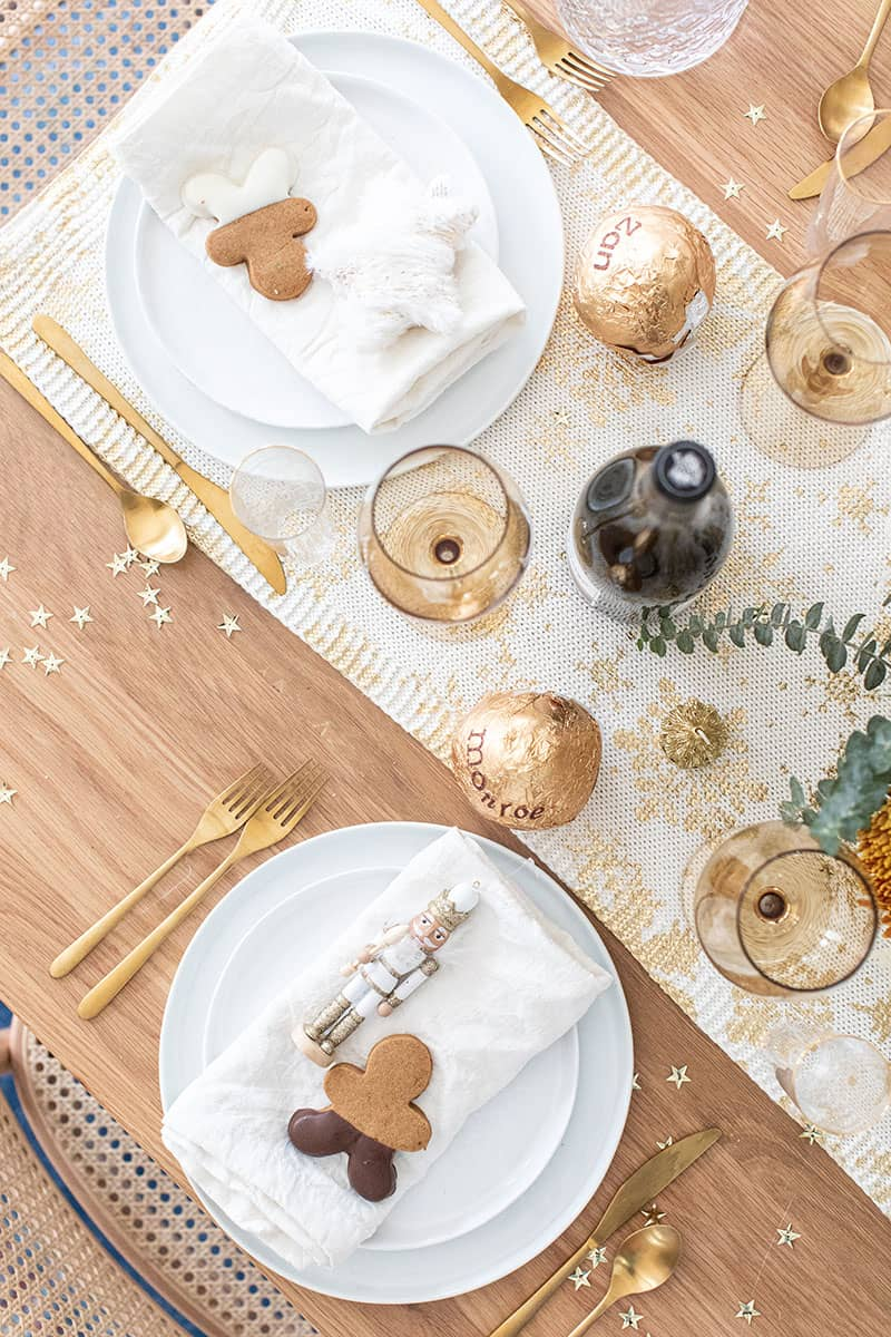 Christmas brunch table setting with gold table runner, gold stars, flowers and gingerbread cookie.