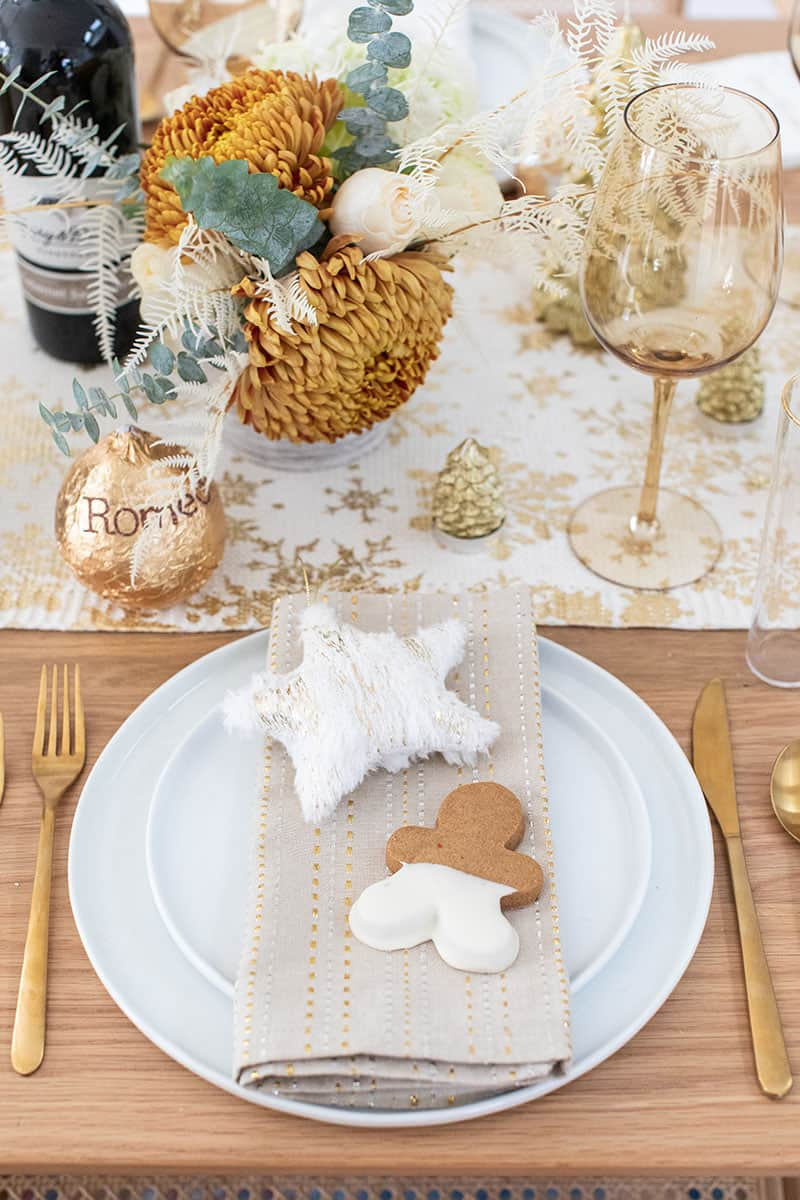 Christmas brunch table setting with flowers, napkins wine glasses.