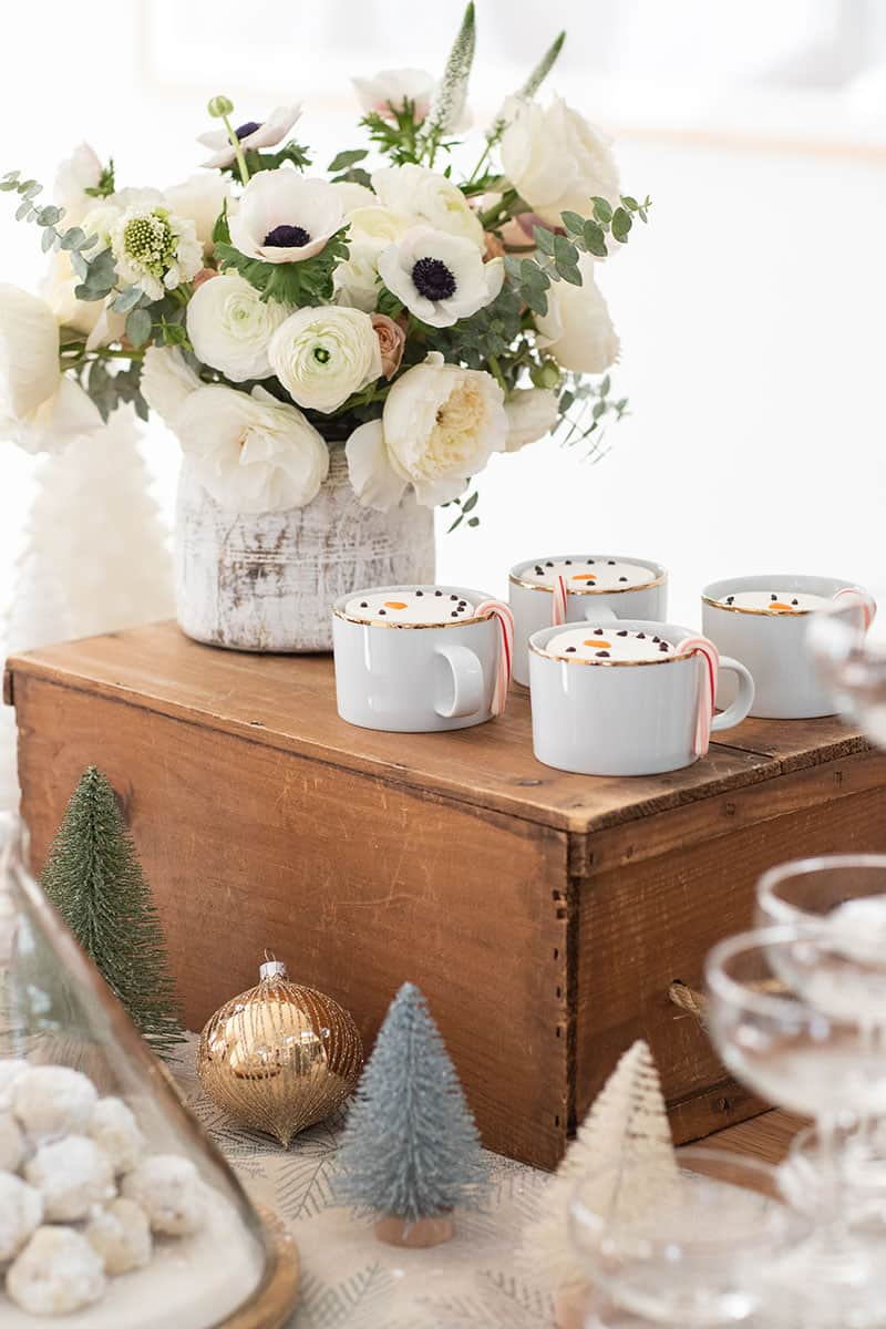 White flowers and gold cups filled with hot chocolate and snowman marshmallows.