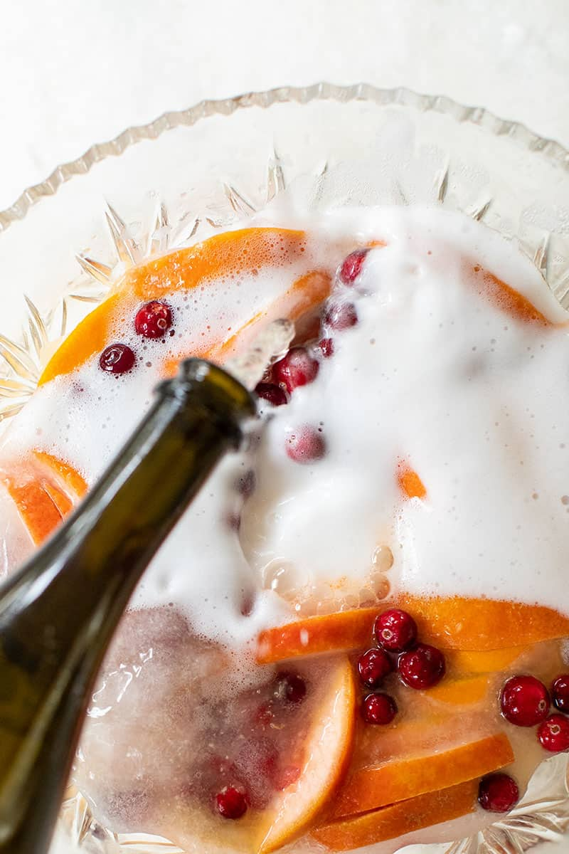 Prosecco being poured into a punch bowl with oranges, cranberries and grapefruit for a citrus holiday punch.