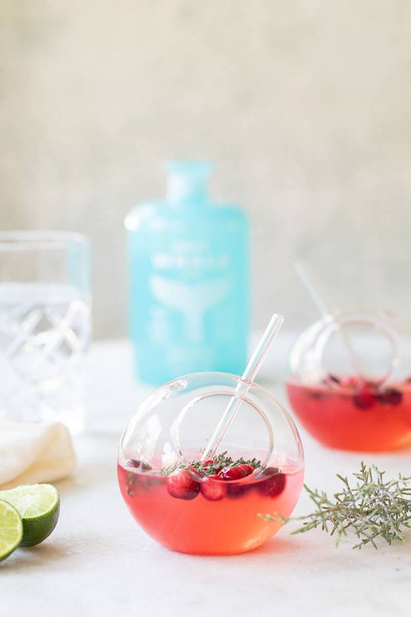 Gin and tonic is a round glass with gray whale gin and lime, cranberries and fresh thyme